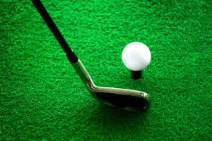 Golf club and ball lined up for swing