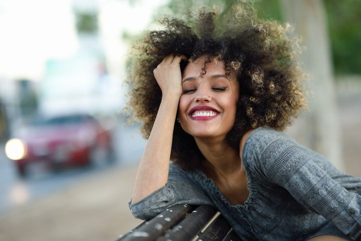 Happy woman with hand in her hair sitting on a park bench