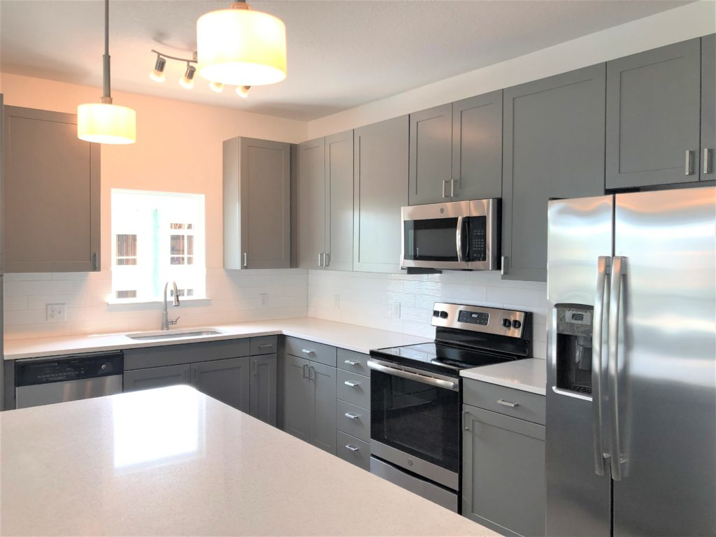 Kitchen with white counter tops and gray cabinets.