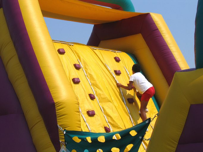 Child climbing up an inflatable climbing wall