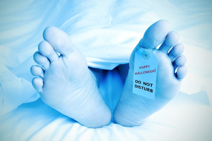 closeup of the feet of a dead body covered with a sheet and with a tag tied on his big toe with the text happy halloween, do not disturb
