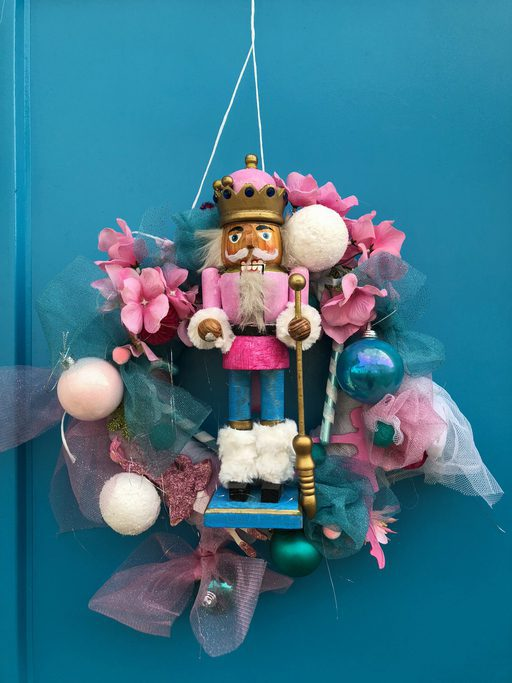Christmas wreath with a figure of a nutcrack hanging on a wooden door
