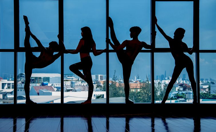 Silhouettes of dancers in dark studio