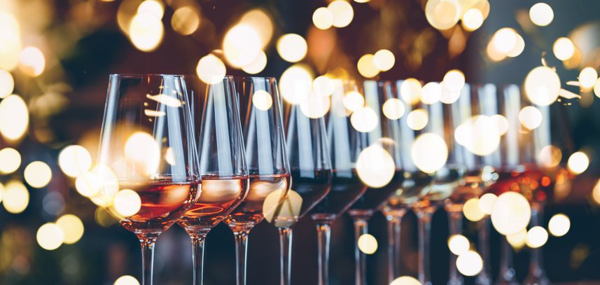 Wine glasses in a row. Buffet table celebration of wine tasting. Nightlife, celebration and entertainment concept. Horizontal, cold toned image, wide screen banner format, bright lights bokeh background