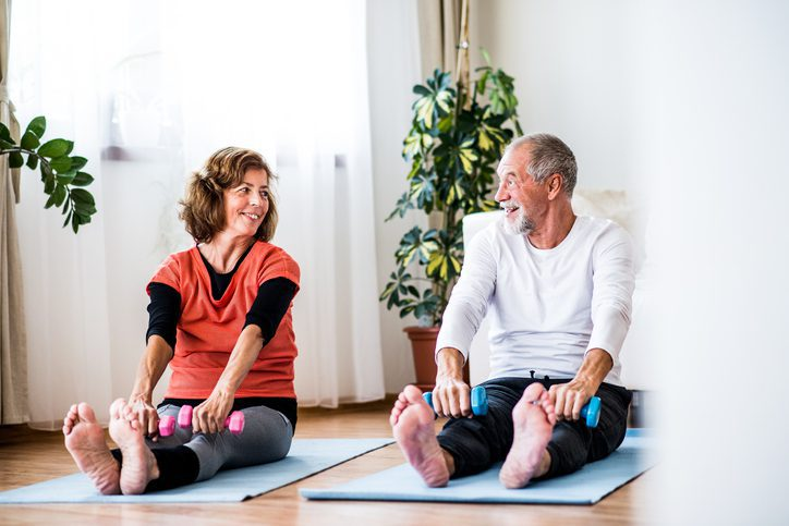 A happy senior couple with dumbbells doing exercise at home.