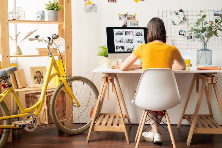 Rear view of young brunette female sitting on white chair in front of computer monitor while looking throguh collection of photos