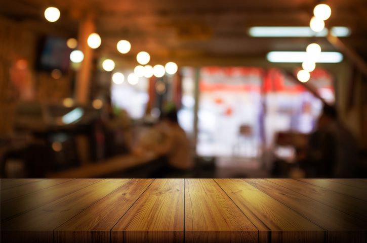 Empty wooden table top with blurred coffee shop or restaurant interior background. Abstract background can be used for display or montage your products.