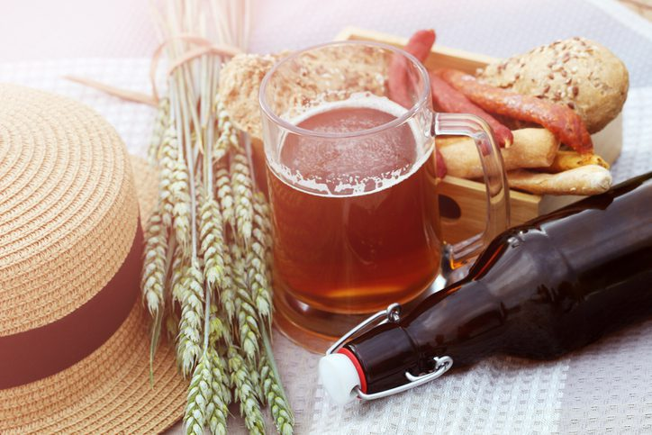 A mug of fresh craft beer without foam,a glass beer bottle with a bugle stopper, wheat, smoked sausages and bread in the open air during the day.Brewing.German-style.International
